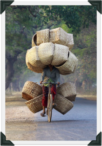 heres-a-woman-biking-with-baskets-to-sell-in-a-market-in-myanmar